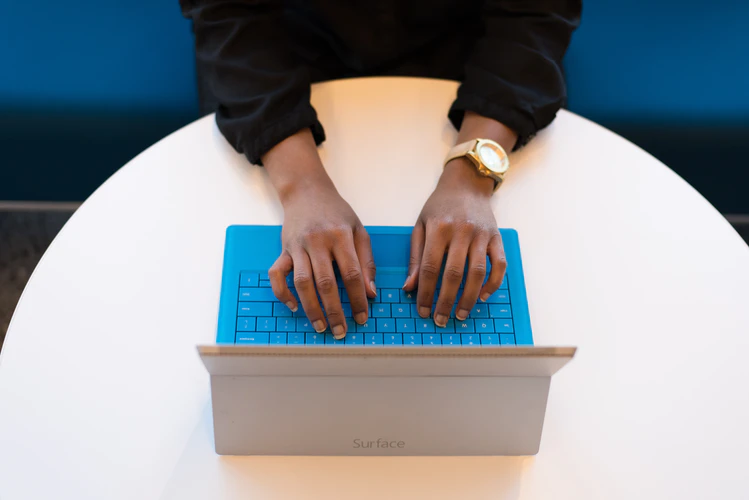 Employee types on blue keyboard Surface tablet